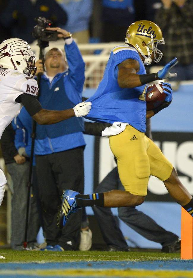 UCLA wide receiver Shaquelle Evans, right, scores a touchdown as Arizona State defensive back Damarious Randall defends during the second half an NCAA college football game, Saturday, Nov. 23, 2013, in Pasadena, Calif