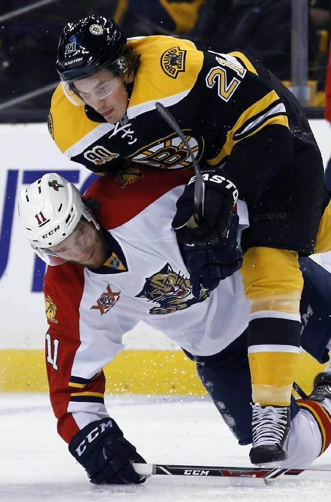 Boston Bruins left wing Loui Eriksson (21) gets tangled up with Florida Panthers center Jonathan Huberdeau (11) as they go for the puck during the third period of an NHL hockey game in Boston, Tuesday, Jan. 28, 2014. The Bruins won 6-2
