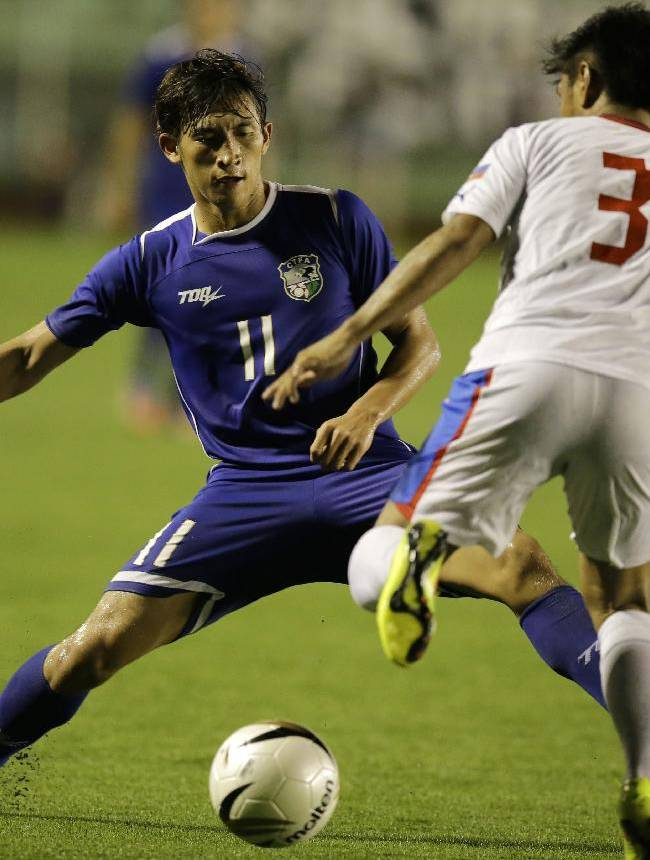 The Philippines' Daisuke Sato (3) and Taiwan's Li Mao (11) battle for the ball during the Peace Cup 2014 soccer friendly match Wednesday, Sept.3, 2014 at the rain-soaked Rizal Memorial Football Stadium in Manila, Philippines