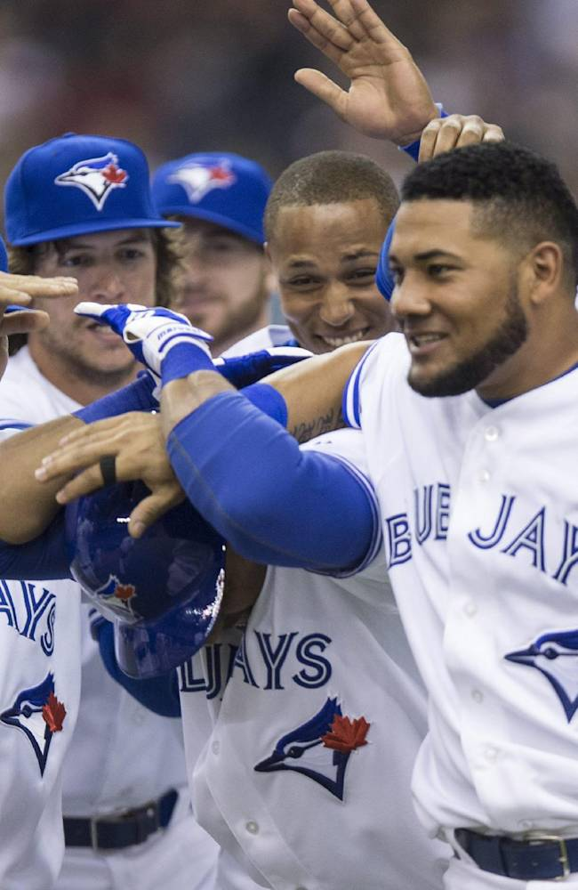 Toronto Blue Jays' Ricardo Nanita, right,  is congratulated by teammates after hitting a single scoring Munenori Kawasaki to beat the New York Mets 5-4 in the ninth inning Friday, March 28, 2014 in Montreal