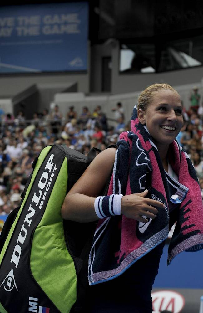 Dominika Cibulkova of Slovakia smiles as she leaves the court following her win over Carla Suarez Navarro of Spain during their third round match at the Australian Open tennis championship in Melbourne, Australia, Saturday, Jan. 18, 2014
