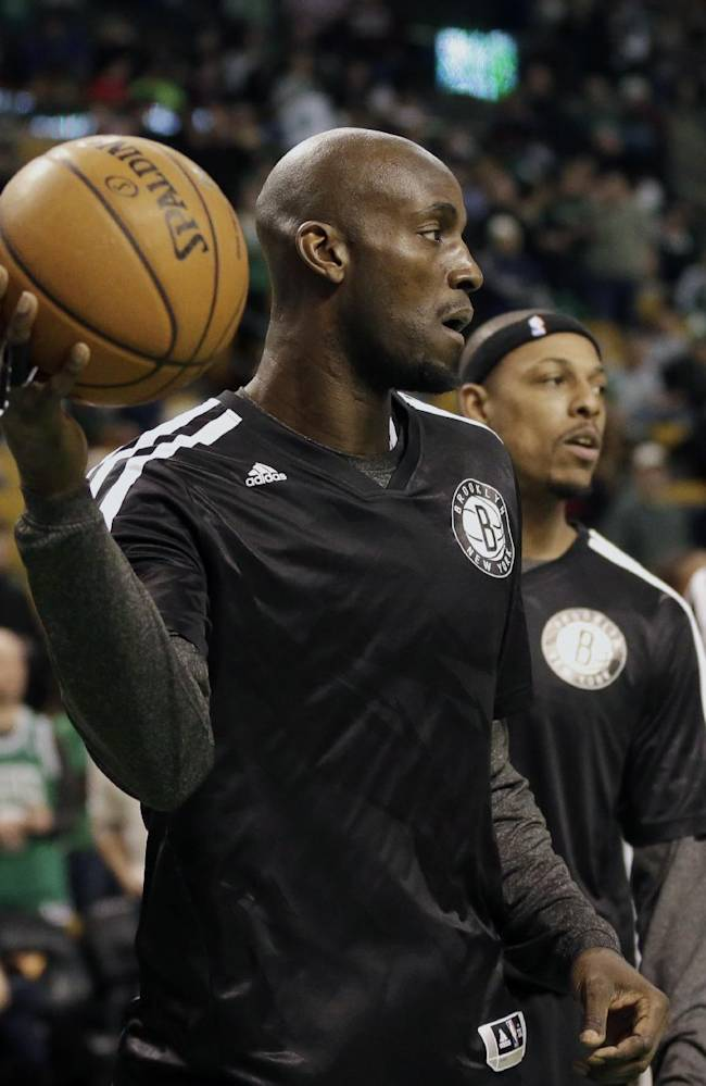 Brooklyn Nets forward Kevin Garnett, left, and forward Paul Pierce, right, both former Boston Celtics players, warm up before an NBA basketball game against the Celtics, Sunday, Jan. 26, 2014, in Boston