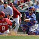 St. Louis Cardinals' Peter Bourjos, left, scores as the throw gets away from New York Mets catcher Travis d'Arnaud during the fifth inning of an exhibition baseball game Sunday, March 2, 2014, in Jupiter, Fla The Associated Press