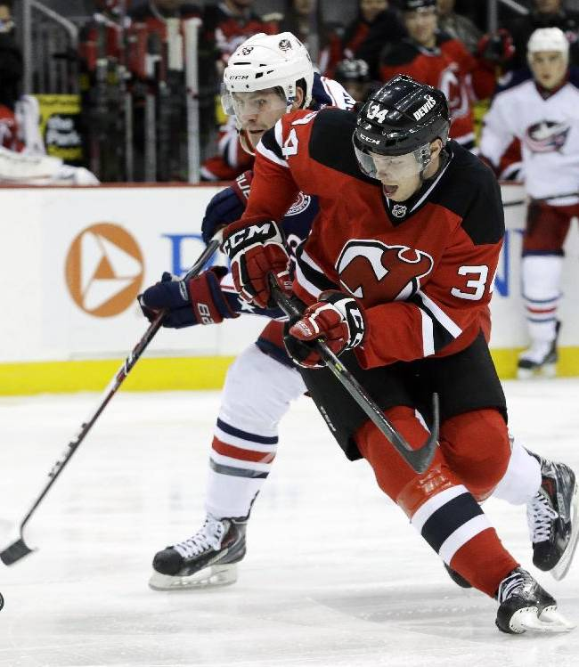 New Jersey Devils' Jon Merrill (34) and Columbus Blue Jackets' Boone Jenner compete for the puck during the first period of an NHL hockey game, Friday, Dec. 27, 2013, in Newark, N.J