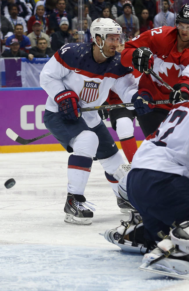 Canada forward Benn Jamie, right, shoots and scores against USA goaltender Jonathan Quick during the second period of a men's semifinal ice hockey game at the 2014 Winter Olympics, Friday, Feb. 21, 2014, in Sochi, Russia. (AP Photo/Julio Cortez)