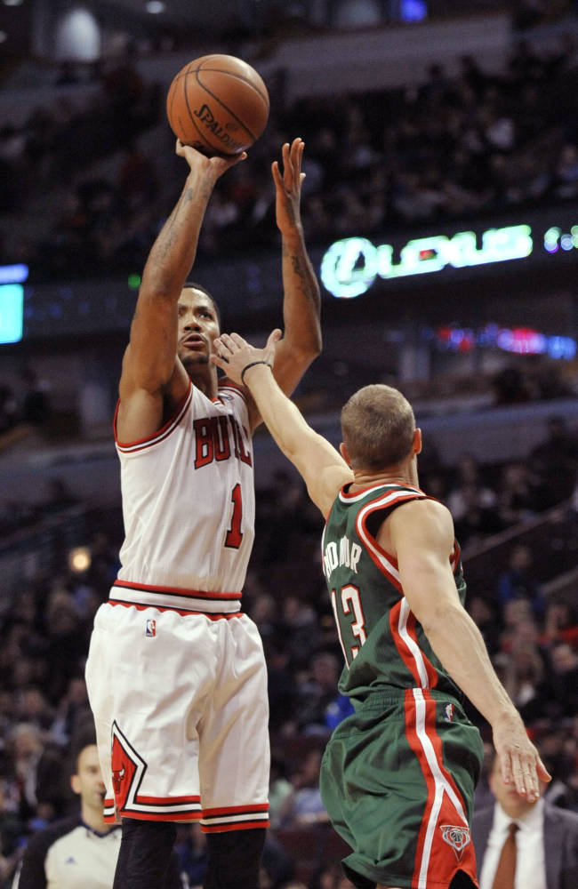Chicago Bulls' Derrick Rose (1), goes up for a shot against Milwaukee Bucks' Luke Ridnour (13), during the second half of an NBA preseason basketball game in Chicago, Monday, Oct. 21, 2013. Chicago won 105-84