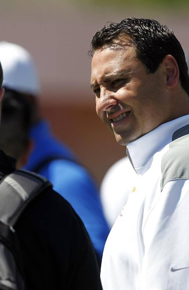 Southern California coach Steve Sarkisian talks to an NFL scout during Southern California's pro day at Loker Field on Wednesday, March 12, 2014, in Los Angeles