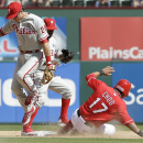 Philadelphia Phillies second baseman Chase Utley (26) tags Texas Rangers' Shin-Soo Choo (17) out at second during the seventh inning of an opening day baseball game at Globe Life Park, Monday, March 31, 2014, in Arlington, Texas The Associated Press
