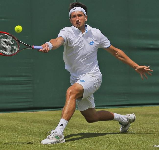 Sergiy Stakhovsky of Ukraine plays a return to Ernests Gulbis of Latvia during their men's singles match match at the All England Lawn Tennis Championships in Wimbledon, London, Wednesday, June 25, 2014