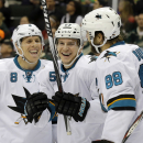 San Jose Sharks center Joe Pavelski, left, and defenseman Brent Burns (88) congratulate center Tommy Wingels, center, after Wingels scored against Minnesota Wild goalie Darcy Kuemper during the second period of an NHL hockey game in St. Paul, Minn., Thurs