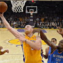 Los Angeles Lakers center Chris Kaman, center, puts up a shot as Oklahoma City Thunder power forward Serge Ibaka, of Congo, defends during the second half of an NBA basketball game, Thursday, Feb. 13, 2014, in Los Angeles The Associated Press