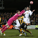 Cambridge United's goalkeeper Chris Dunn, left punches the ball clear as Manchester United's Robin Van Persie heads for goal during their English FA Cup fourth round soccer match between Cambridge United and Manchester United, in Cambridge, England, Frida