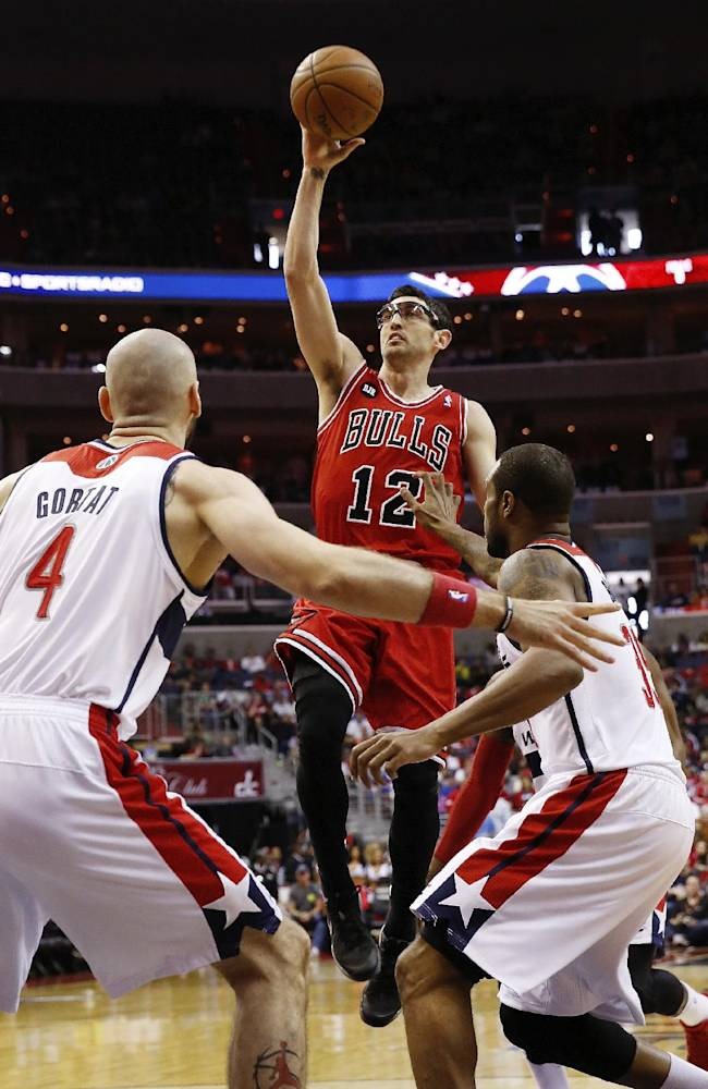 Chicago Bulls guard Kirk Hinrich (12) shoots over Washington Wizards center Marcin Gortat (4), from Poland, and Trevor Booker, right, during the first half of game 4 of an opening-round NBA basketball playoff series in Washington, Sunday, April 27, 2014
