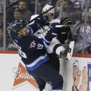 Winnipeg Jets' Jim Slater (19) checks Pittsburgh Penguins' Paul Martin during the second period of an NHL hockey game in Winnipeg, Manitoba, on Thursday, April 3, 2014 The Associated Press