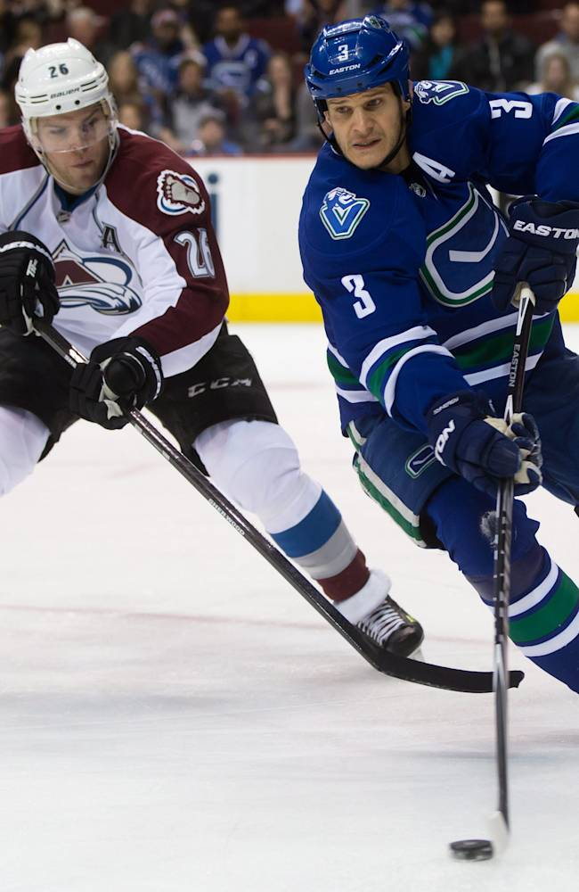 Vancouver Canucks' Kevin Bieksa, right, skates with the puck as Colorado Avalanche's Paul Stastny gives chase during the first period of an NHL hockey game Thursday, April 10, 2014, in Vancouver, British Columbia