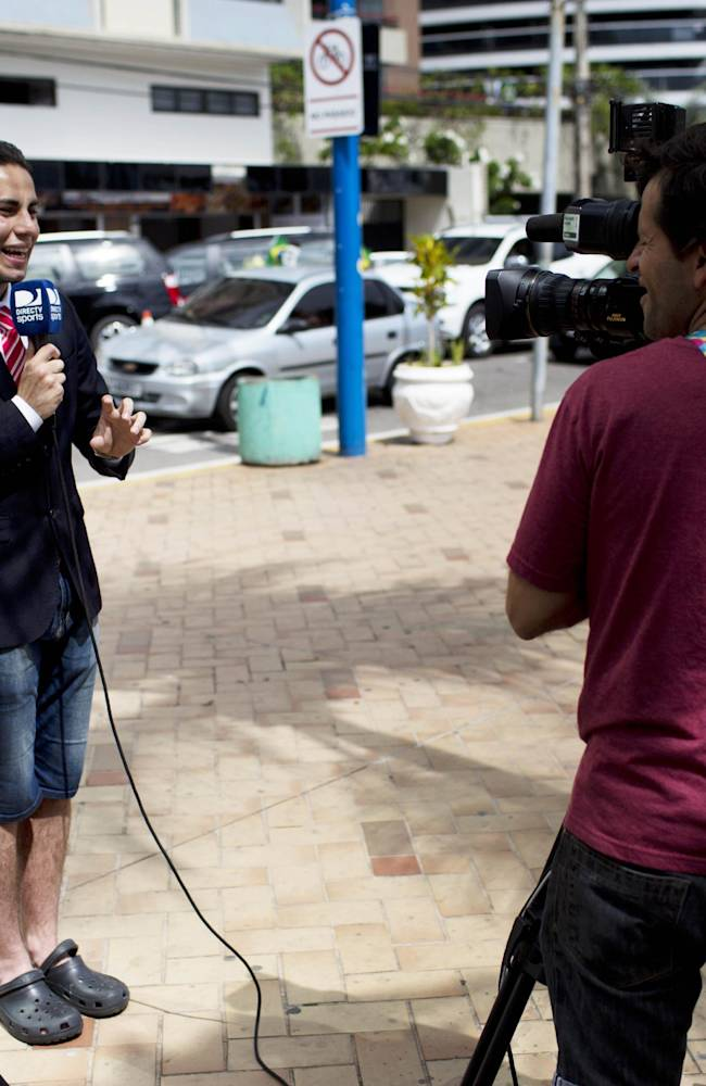 A Colombian TV reporter works in front of the hotel where the Colombian national soccer team is staying, in Fortaleza, Brazil, Thursday, July 3, 2014. Colombian supporters are in Fortaleza hoping to see some history being made in this northeastern World Cup city where Brazil and Colombia face off in the World Cup quarterfinals, Saturday