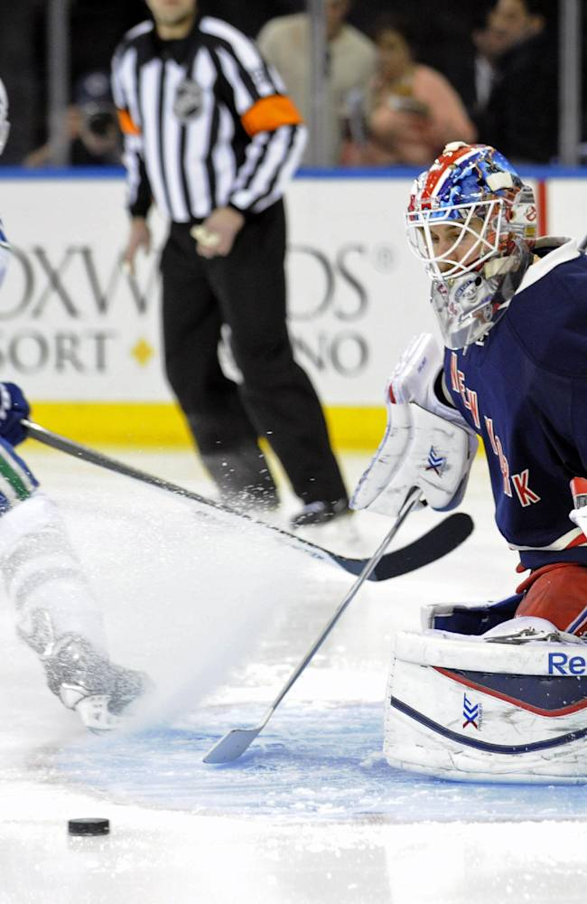 New York Rangers goaltender Cam Talbot, right, makes a save on a shot by Vancouver Canucks' Ryan Kesler during the first period of an NHL hockey game Saturday, Nov. 30, 2013, at Madison Square Garden in New York