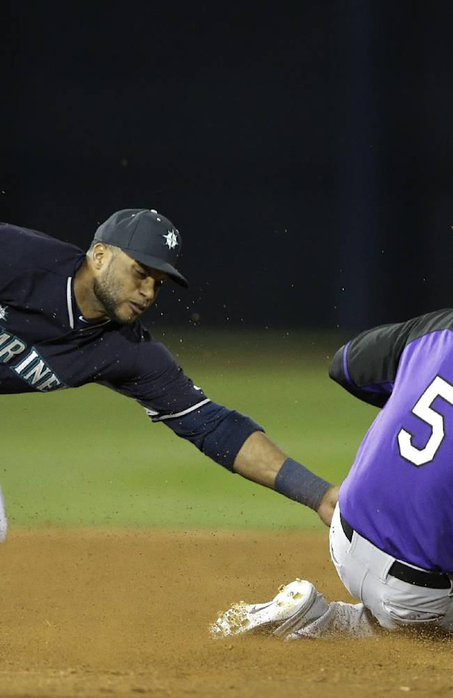 Colorado Rockies' Carlos Gonzalez is tagged out by Seattle Mariners second baseman Robinson Cano trying to steal second during the third inning of an exhibition baseball game Friday, March 28, 2014, in Peoria, Ariz