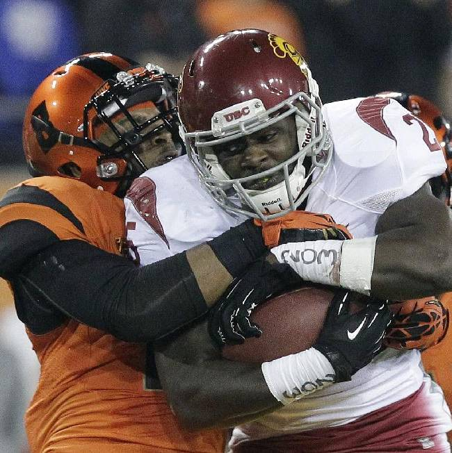 CORRECTS OREGON STATE ID TO TYREQUEK ZIMMERMAN, INSTEAD OF RICHARD MULLANEY - Southern California running back Silas Redd, right, is tackled by Oregon State defender Tyrequek Zimmerman during the first half of an NCAA college football game in Corvallis, Ore., Friday, Nov. 1, 2013