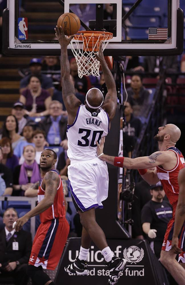 Sacramento Kings forward Reggie Evans, center, goes to the basket between Washington Wizards' Trevor Booker, left, and Marcin Gortat, of Poland during the first quarter of an NBA basketball game in Sacramento, Calif., Tuesday, March 18, 2014