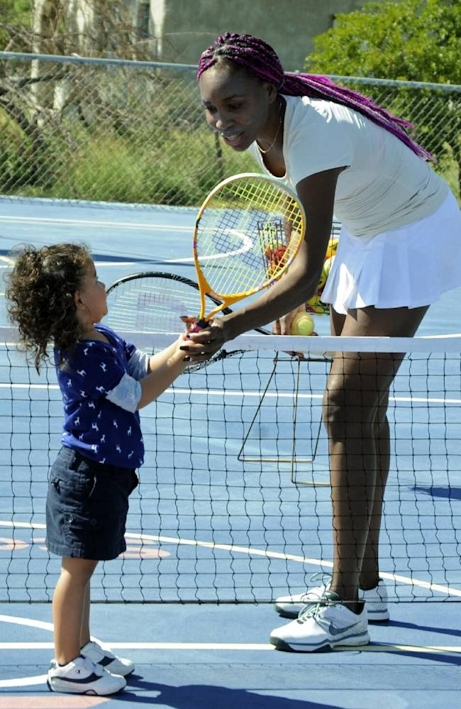 Venus Williams instructs 3-year-old Rebecca Moulton during a tennis clinic in St. Elizabeth, southwestern Jamaica, Saturday, Nov. 23, 2013. Venus and Serena Williams, who are vacationing in Jamaica, offered part of their time to interact with young local players