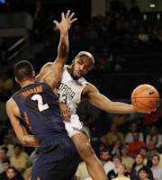 Georgia Tech guard Trae Golden, right, passes the ball as Illinois guard Joseph Bertrand (2) defends in the first half of an NCAA college basketball game Tuesday, Dec. 3, 2013, in Atlanta. (AP Photo/John Bazemore)