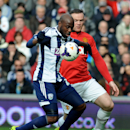 West Brom's Youssuf Mulumbu shields the ball from Manchester United's Wayne Rooney during the English Premier League soccer match between West Bromwich Albion and Manchester United at The Hawthorns Stadium in West Bromwich, England, Saturday, March 8, 201