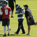 Philadelphia Eagles head coach Chip Kelly gestures as running back LeSean McCoy, center, walks by as quarterback Nick Foles (9) looks on during NFL football practice at the team's training facility, Tuesday, Sept. 23, 2014, in Philadelphia. The Associated