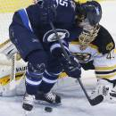 Winnipeg Jets' Mathieu Perreault (85) attempts a backhander against Boston Bruins goaltender Tuukka Rask (40) during the first period of an NHL hockey game Friday, Dec. 19, 2014, in Winnipeg, Manitoba. (AP Photo/The Canadian Press, John Woods)