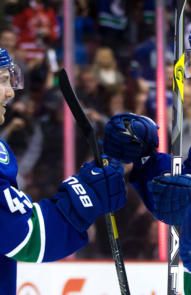 Vancouver Canucks' Jordan Schroeder, left, and David Booth celebrate Schroeder's goal against the Edmonton Oilers during first period of an NHL hockey game in Vancouver, British Columbia, on Monday, Jan. 27, 2014