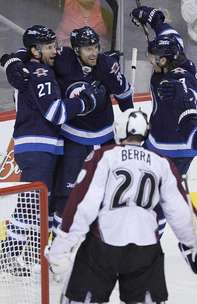Winnipeg Jets' Eric Tangradi (27), Blake Wheeler (26) and Keaton Ellerby celebrate Tangradi's goal against Colorado Avalanche goaltender Reto Berra (20) during the first period of an NHL hockey game Wednesday, March 19, 2014, in Winnipeg, Manitoba