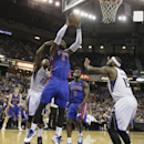 Detroit Pistons center Andre Drummond, center, goes the the basket against Sacramento Kings' Marcus Thornton, left, and DeMarcus Cousins, right, during the fourth quarter of an NBA basketball game in Sacramento, Calif., Friday, Nov. 15, 2013. The Pist