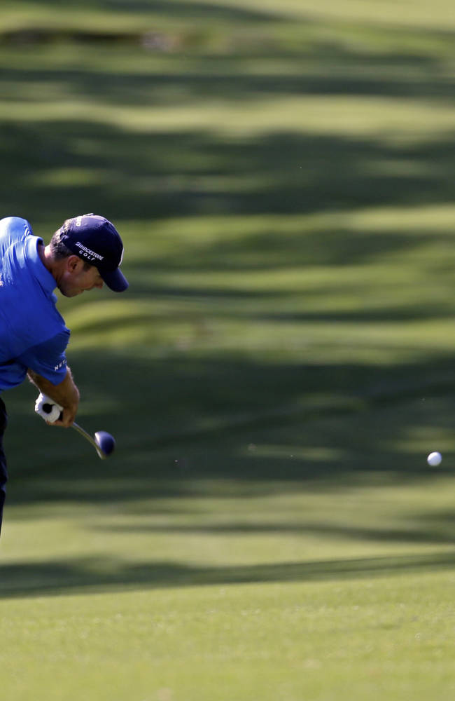 Matt Kuchar takes his second shot on the 18th fairway during the third round of the Masters golf tournament Saturday, April 12, 2014, in Augusta, Ga