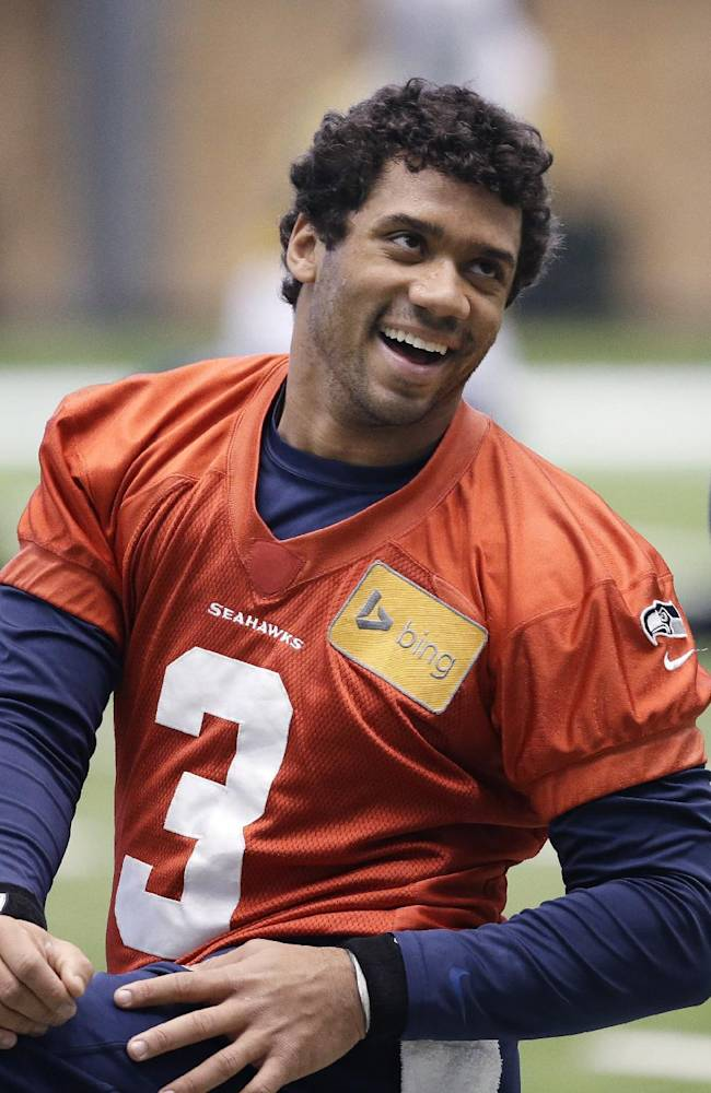 Seattle Seahawks quarterback Russell Wilson smiles as he stretches for NFL football practice Tuesday, Jan. 7, 2014, in Kirkland, Wash. The Seahawks play the New Orleans Saints Saturday in an NFC divisional playoff game