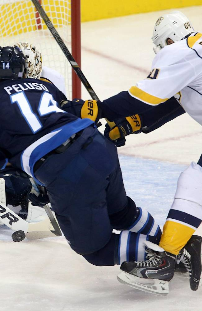 Winnipeg Jets' Anthony Peluso (14) is tripped by Nashville Predators' Victor Bartley (64) in front of goaltender Carter Hutton (30) during first period NHL hockey game in Winnipeg, Manitoba, Sunday, Oct. 20, 2013