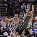 San Antonio Spurs' Tony Parker (9), of France, drives around Utah Jazz's Trey Burke (3) during the first half of an NBA basketball game, Sunday, March 16, 2014, in San Antonio. (AP Photo/Eric Gay)