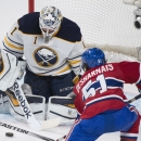 Buffalo Sabres goaltender Jhonas Enroth, left, makes a save against Montreal Canadiens' David Desharnais during second-period NHL hockey game action in Montreal, Saturday, Nov. 29, 2014 The Associated Press