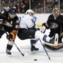 Anaheim Ducks' Francois Beauchemin, left, and San Jose Sharks' Patrick Marleau, center, compete for the puck in front of Anaheim Ducks goalie Frederik Andersen, of Denmark, during the third period of an NHL hockey game Sunday, Oct. 26, 2014, in Anaheim, C