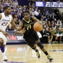 Oregon's Damyean Dotson (21) drives around Washington's C.J. Wilcox (23) in the first half of an NCAA college basketball game, Wednesday, Feb. 13, 2013, in Seattle. (AP Photo/Ted S. Warren)