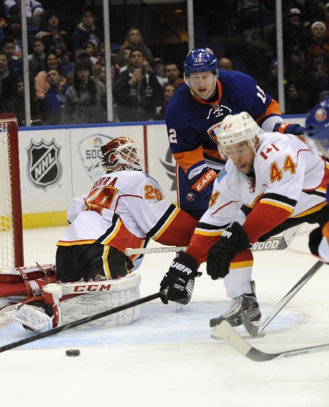 New York Islanders' Thomas Hickey (14) shoots the puck past Calgary Flames' Chris Butler (44) and Calgary Flames goalie Reto Berra (29) to score as Islanders' Josh Bailey (12) watches from behind in the second period of an NHL hockey game, Thursday, Feb. 6, 2014, in Uniondale, N.Y