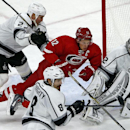 Carolina Hurricanes' Eric Staal (12) is sent crashing into Los Angeles Kings goalie Jonathan Quick (32) by Kings Matt Greene (2) as the puck leaves the area and Kings Drew Doughty (8) gives chase during the third period of an NHL hockey game in Raleigh, N