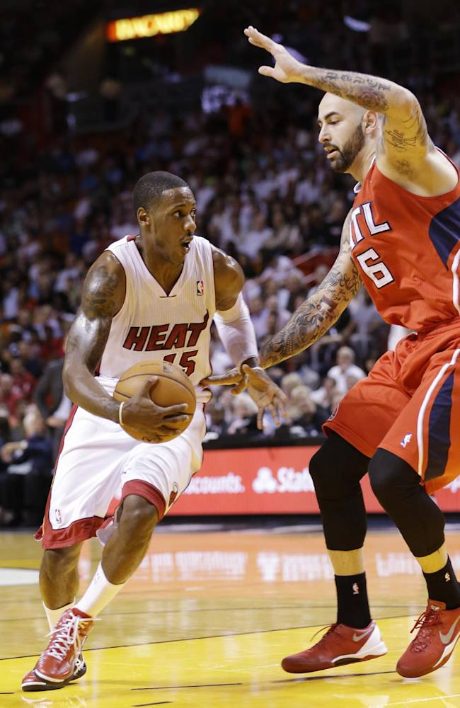 Miami Heat guard Mario Chalmers (15) drives past Atlanta Hawks center Pero Antic (6) of Macedonia, during the first half of an NBA basketball game, Tuesday, Nov. 19, 2013 in Miami. The Heat defeated the Hawks 104-88