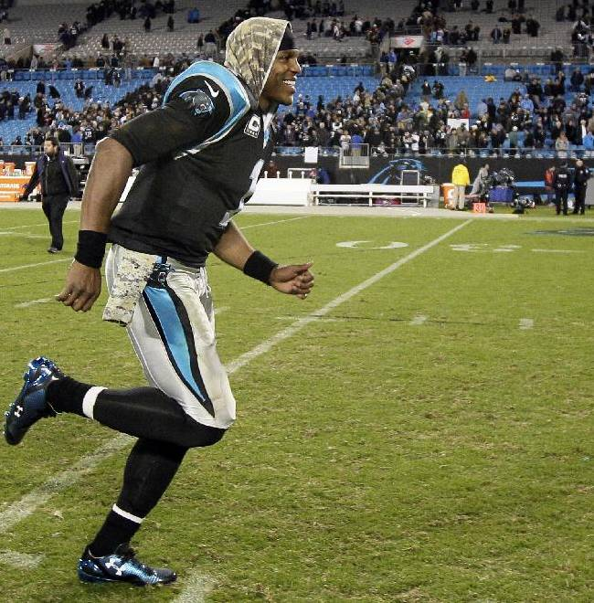 Carolina Panthers quarterback Cam Newton smiles as he runs off the field following Carolina's 24-20 win over the New England Patriots following an NFL football game in Charlotte, N.C., Monday, Nov. 18, 2013