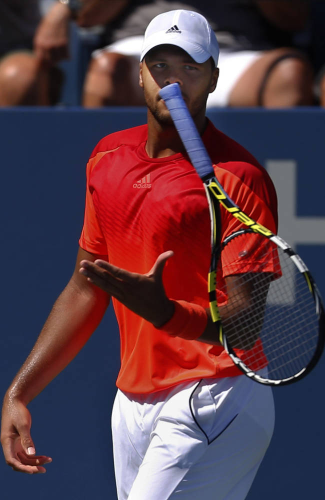 Jo-Wilifried Tsonga, of France, flips his racket after a shot against Juan Monaco, of Argentina, during the opening round of the 2014 U.S. Open tennis tournament, Monday, Aug. 25, 2014, in New York