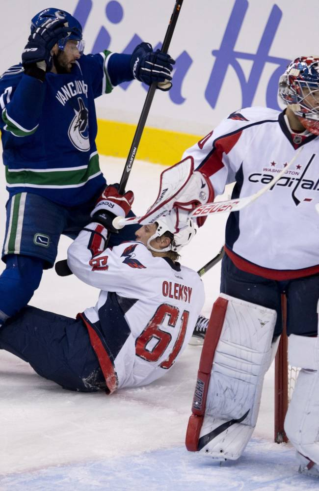 Vancouver Canucks center Ryan Kesler (17) gets caught up on Washington Capitals defenceman Steve Oleksy (61) as Washington Capitals goalie Michal Neuvirth (30) looks on during the second period of NHL hockey action in Vancouver, British Columbia on Monday, Oct. 28, 2013