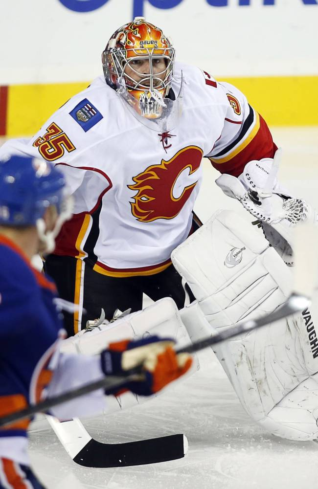 New York Islanders' Peter Regin, left, from Denmark, chases a rebound from Calgary Flames goalie Joey MacDonald during the third period of a preseason NHL hockey game Tuesday, Sept. 17, 2013, in Calgary, Alberta. Calgary won 5-3
