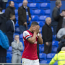 Arsenal's Alex Oxlade-Chamberlain covers his face as he walks from the pitch after his team's 3-0 loss at Everton in their English Premier League soccer match at Goodison Park Stadium, Liverpool, England, Sunday April 6, 2014