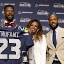 Seattle Seahawks' Marcus Trufant, left, holds up a team jersey as he stands with his wife Jessica and brothers Isaiah, second right, and Desmond to start a news conference announcing his retirement from football after signing with the team a day earlier, Thursday, April 24, 2014, in Renton, Wash. Trufant started 125 games in a Seattle career that lasted from 2003 to 2012. The cornerback was a first-round pick in 2003 out of Washington State and immediately moved into the starting lineup, playing a key role on the 2005 team that advanced to the franchise's first Super Bowl. (AP Photo/Elaine Thompson)