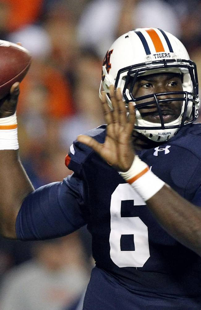 In this Oct. 26, 2013, file photo, Auburn quarterback Jeremy Johnson rolls out to pass during the first half of an NCAA college football game against Florida Atlantic in Auburn, Ala.  Johnson says he has no idea if he's starting against Arkansas with starter Nick Marshall being held out for at least the opening. He does have one prediction: Marshall will win the Heisman Trophy