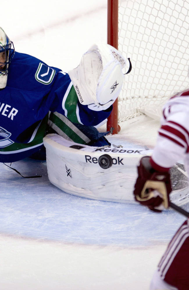 Vancouver Canucks goalie Roberto Luongo (1) stops a shot from Phoenix Coyotes right wing Radim Vrbata (17) during the first period of NHL preseason hockey action at Rogers Arena in Vancouver, British Columbia, Monday, Sept. 23, 2013